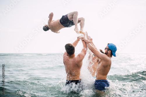 Foto op Plexiglas Water Group of friends throw their friend into water