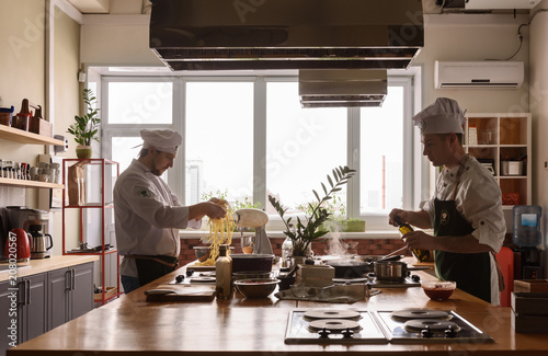 Two cooks on kitchen of restaurant