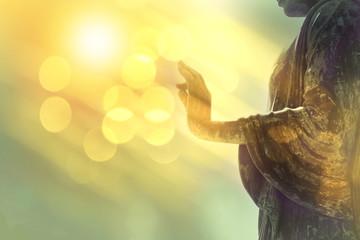 ruka kipa Bude sa žutom bokeh pozadinom, svjetlošću mudrosti i konceptom koncentracije