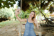 Young happy woman riding swing and making selfie by smartphone, sand and trees in background. Concept of summer vacations and modern technlogy, leisure time.