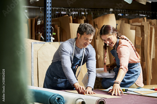 Fotobehang Stof Workers Adjusting Cardboard Paper On Fabric In Sofa Workshop