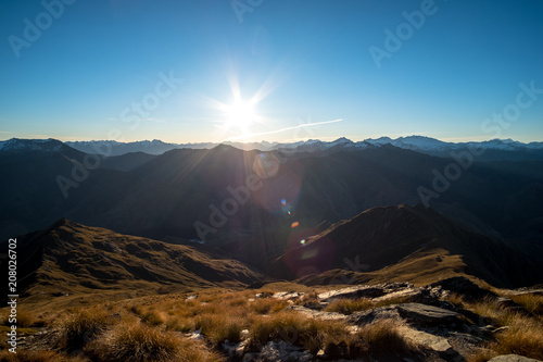 Fotobehang Blauwe jeans Beautiful landscape of a yellow grassland blue sky and Alps mountain at sunset.