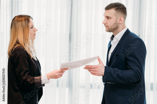 woman handing her letter of resignation to a strict boss ...