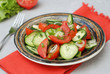 Tomato and cucumber salad vegan food with fork gray textured cement background