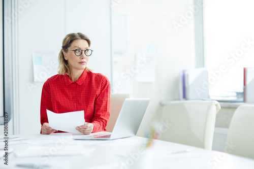 Fotografija Beautiful emotionless woman in red shirt and eyeglasses sitting at table with papers in white light office looking away