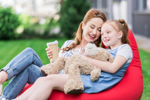 Smiling Mother With Coffee To Go And Daughter With Teddy Bear Resting On Bean Bag Chair Together
