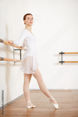 Fotografia  Adult ballerina with ginger and strict hairstyle training dances in light studio