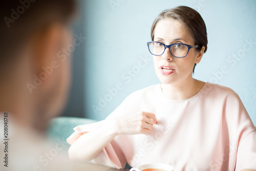 Fototapeta Attractive woman in stylish glasses having serious conversation with employee