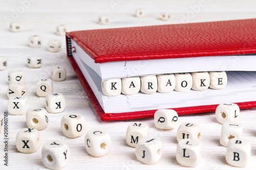 Fotografia, Obraz  Word Karaoke written in wooden blocks in red notebook on white wooden table