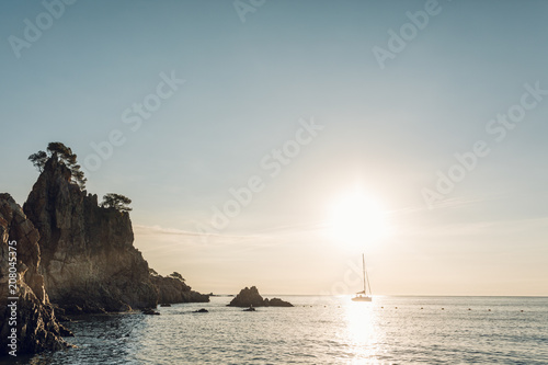 Foto op Plexiglas Zonsondergang Amazing seascape at sunrise of a Sailboat in a tranquil water