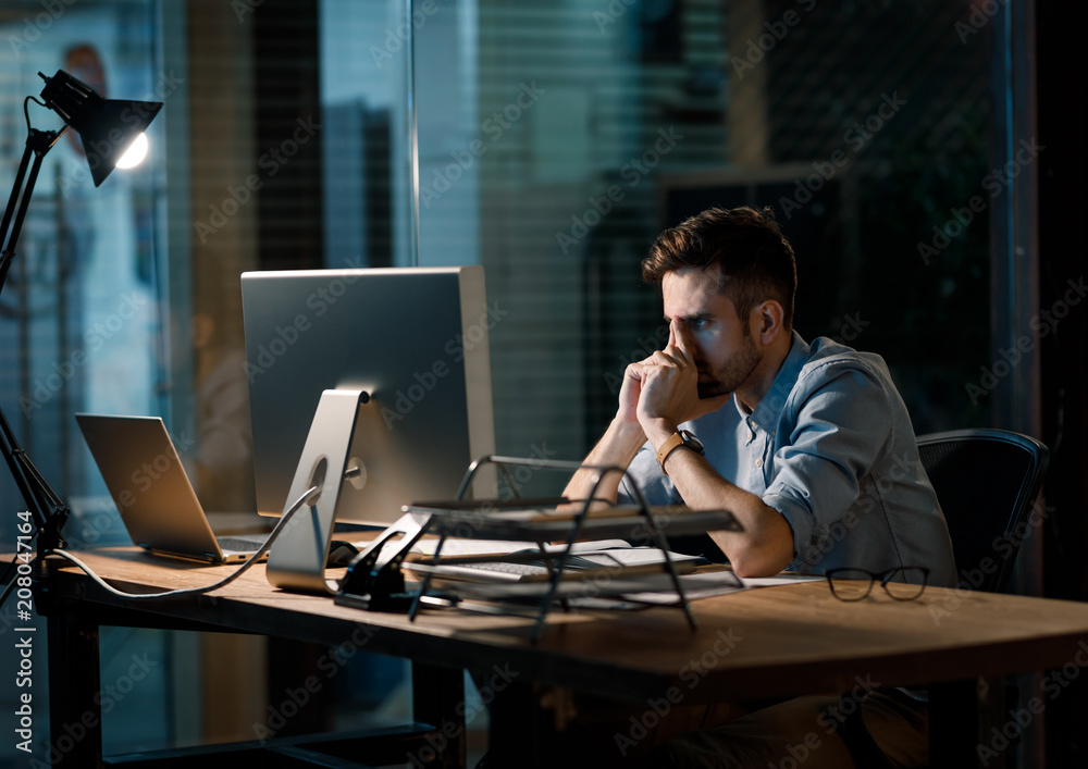 Fototapeta Casual man holding hands on face trying to concentrate on work watching computer at working desk in office.
