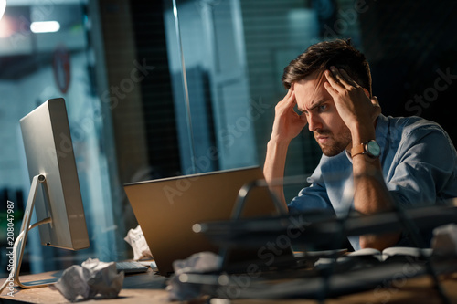Fotografie, Obraz  Young man trying to concentrate on problem while working at table in office and