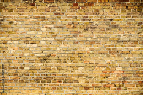 Old and weathered grungy yellow and red brick wall as seamless pattern texture background.