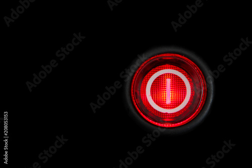 Round red power (on and off) button or switch with retro illumination glowing in the dark macro photography and isolated on a dark black background Tapéta, Fotótapéta