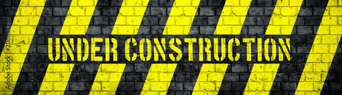 Under construction warning sign with yellow and black stripes on concrete wall texture background in wide panorama format. Concept for do not enter the area, caution, danger, construction site.