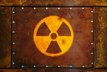 Round Yellow Radioactive (ionizing Radiation) Danger Warning Symbol Painted On A Massive Rusty Metal Plate Fixed With Metallic Screws To The Wall And With Dark Rustic Grungy Texture Background.