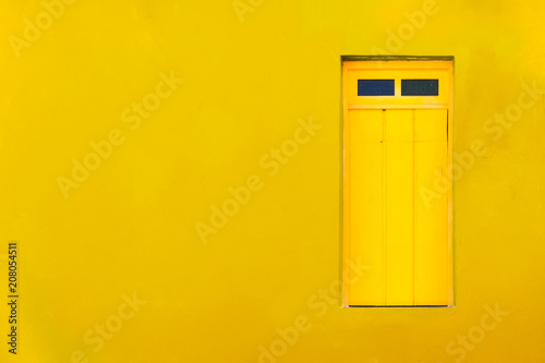 Poster de jardin Havana Colourful colonial Caribbean tropical style yellow facade closed window in a bright and intense yellow wall house background. Minimalist color toned concept image for tropical, summer, Caribbean.