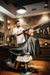 Hairdresser blow drying his client in barbershop. Barber using scissors and comb