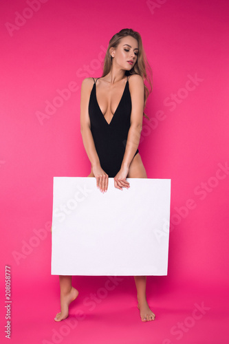 Poster Akt Natural elegance inspires the mind! Full length portrait of the beautiful good-looking young woman in black lingerie standing with white board in the studio.