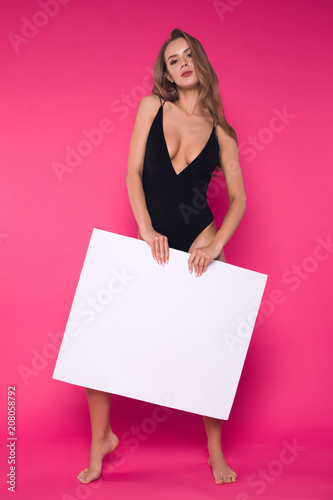 Poster Akt Feel comfortable! Full length picture of the smart attractive girl holding the empty blank board and wearing sexy lingerie on the isolated pink background.