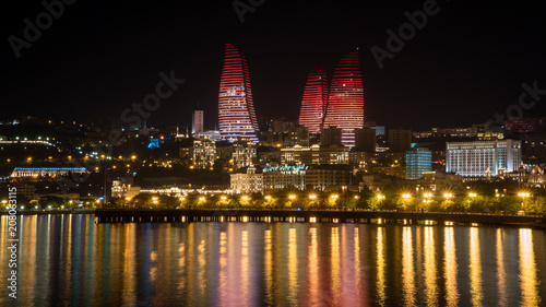 Cuadros en Lienzo  Baku night cityscape with flaming towers and reflections in the Caspian sea bay