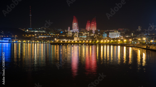 Fotomural  Baku night cityscape with flaming towers and reflections in the Caspian sea bay