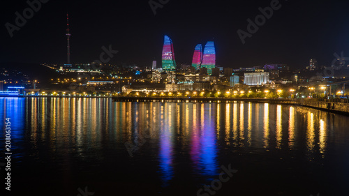 Fotografía  Baku night cityscape with flaming towers and reflections in the Caspian sea bay