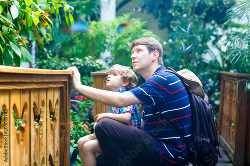 Foto  Father and preschool kid boy discovering flowers, plants and butterflies at botanic garden