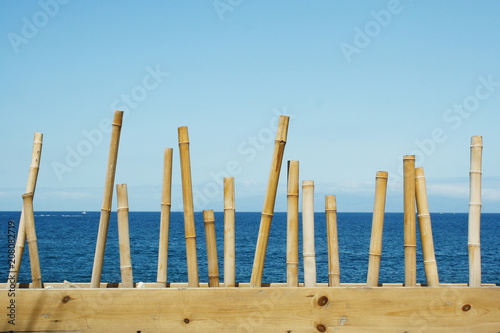 Seascape with the blue sky and the ocean in the background and in the foreground a decoration with bamboo canes in the island of Tenerife