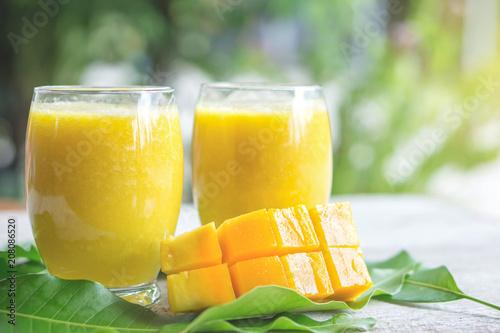 Poster Sap fresh mango juice glasses and green leaf , tropical summer drink in hot season