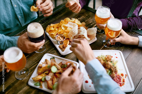 Men Drinking Beer And Eating Food Closeup