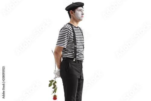Fotografie, Obraz  Sad mime holding a rose behind his back