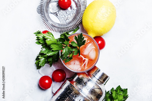Fotobehang Cocktail Bloody mary alcoholic cocktail with red tomato, lemon juice, hot sauce, green celery and russian vodka, gray background, top view