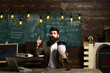 Scientist hipster with lightbulb on chalkboard. Bearded man hold bulb in classroom. Businessman in suit at school desk. Teacher with long beard on genius face. Got idea. enlightenment and invention