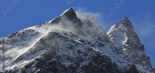 Fotobehang Asia land Strong winds blowing snow over mountain peaks in the Himalayas.