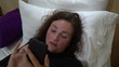 Young beautiful tired woman using smartphone in bed