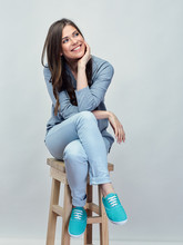 Smiling Young Woman Sitting On Stool With Crossed Legs.