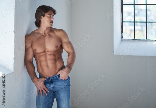 Fotografie, Obraz  Shirtless handsome male with a perfect muscular body leaning on a wall in the studio, looking at a window