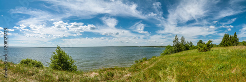 Foto auf Gartenposter Gras summer landscape. panoramic view of the lake under a beautiful cloudy sky with a coast in the foreground