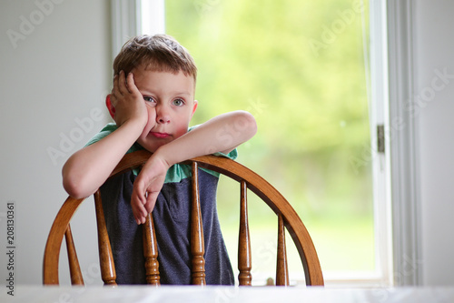 Fotografie, Obraz  bored kid holding hand on cheek. the boy  leaning on a chair