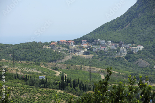 Fotografia, Obraz  View of a small resort town Krasnokamenka situated at a foothill of a mountain, sea in the background