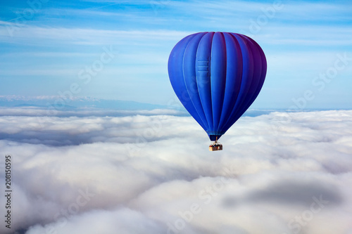 A lonely blue hot air balloon floats above the clouds. Concept leader, success, loneliness, victory
