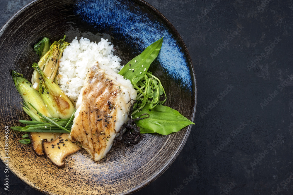Fototapeta Modern Japanese fried cod fish filet with bok choi and rice as top view in a bowl with copy space right
