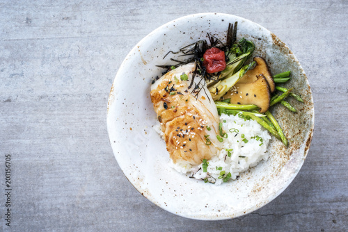 Modern Japanese fried cod fish filet with green asparagus and rice as top view in a bowl with copy space left