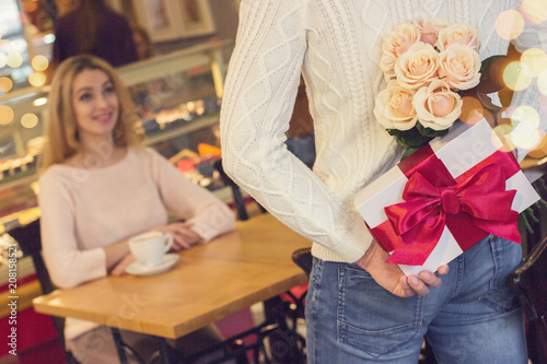 Back view man keeping flower bouquet and gift box behind his back for his beautiful girlfriend in cozy cafe Canvas Print