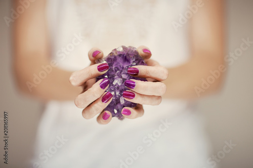 Beautiful woman hands with perfect pink nail polish holding violet amethyst crys Wallpaper Mural