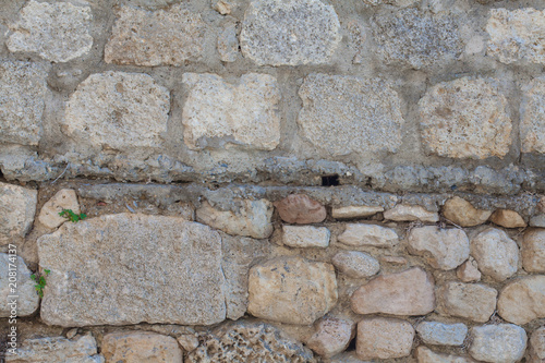 In de dag Stenen The wall is lined with stones. Building with cobblestones. Background of stones. The texture of the walls in the exterior. Natural stone as a building material.