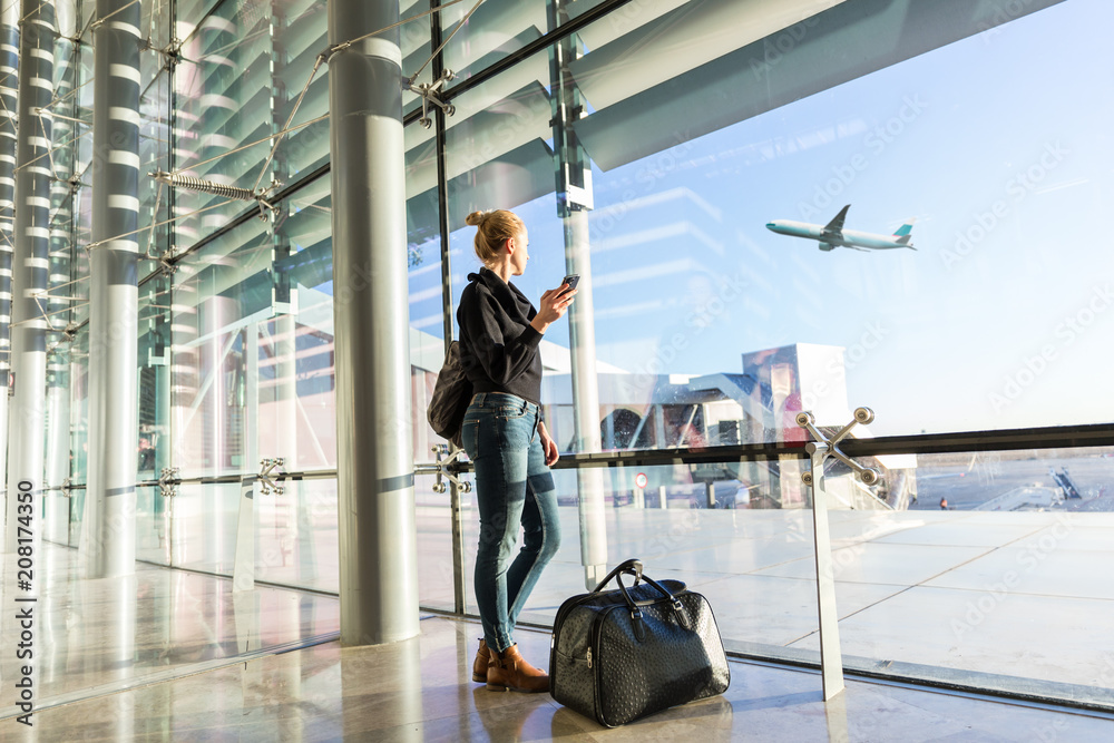 Fototapety, obrazy: Young casual female traveler at airport, holding smart phone device, looking through the airport gate windows at planes on airport runway.