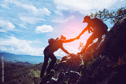 Fototapeta  Two friends helping each other and with teamwork trying to reach the top of the mountains during wonderful summer sunset