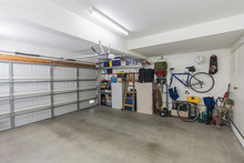 Clean Suburban Two Car Garage Interior With Tools, File Cabinets And Sports Equipment.